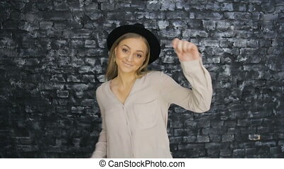 A girl in a black hat is dancing on the background of a textured wall