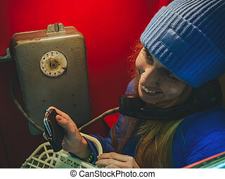 A girl in a blue hat and jacket smiles and talks on a retro telephon hanging on a red wall, holding an old wallet in her hand. Retro Museum.
