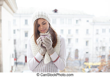 a girl in a CAP stands on the street with a cup of coffee