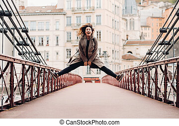 a girl in a coat with her hair down jumps emotionally on a bridge in the old city of Lyon. France. Girl in a coat in France