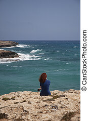 A girl in a dress sits alone on the rocky shore of the turquoise blue sea