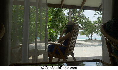 A girl in a hat sitting in a lounge chair on the terrace drinking tea and looking at your mobile phone, writing SMS message.