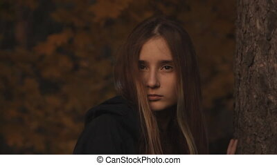 A girl in a hoody with her hair loose to hide a part of her face looking sullenly. A close-up of a girl s face. In a dark forest. Small color correction.