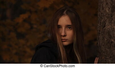 A girl in a hoody with her hair loose to hide a part of her face looking sullenly. In a dark forest. A close-up of a girl s face.