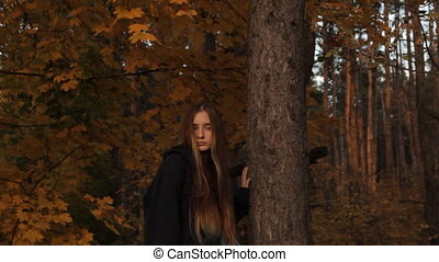 A girl in a hoody with her hair loose who holds a tree with her hand looks around sullenly on the prowl. A midshot of a girl. In a dark forest.