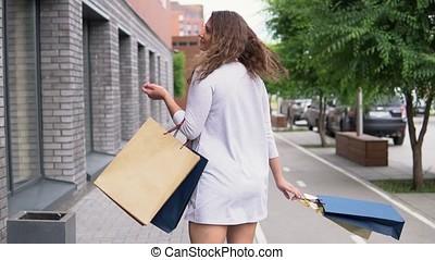 A girl in a light dress goes down the street after shopping having a good mood and carries packages with purchases in her hands. slow motion. HD