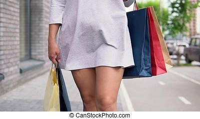 A girl in a light dress goes down the street after shopping having a good mood and carries packages with purchases in her hands. slow motion. Close-up