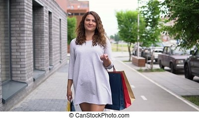 A girl in a light dress is walking down the street after shopping. slow motion.
