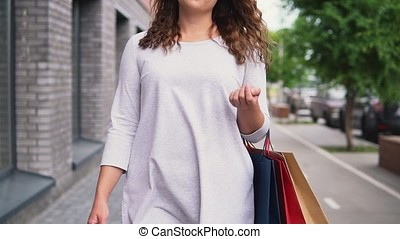 A girl in a light dress with long hair goes down the street after shopping having a good mood and carries packages with purchases in her hands. slow motion. Close-up