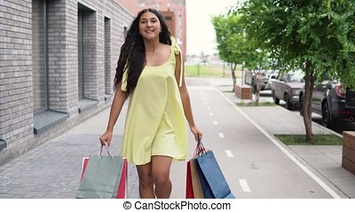 A girl in a long dress goes around the city after shopping having a good mood. 4K