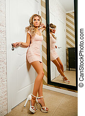 A girl in a pink dress is standing in the hallway next to the mirror.