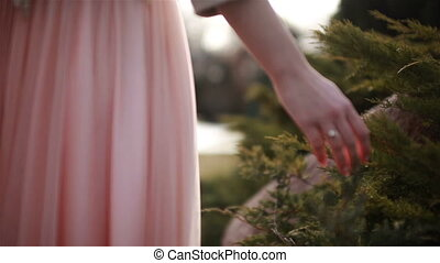 A girl in a pink dress spends her hand on a green bush