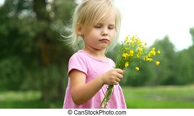 A girl in a pink dress with a bouquet of wild flowers