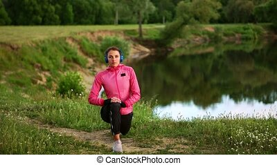 A girl in a pink jacket is preparing for a run warm up and listen to music in headphones through the phone
