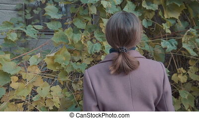A girl in a purple coat stands with her back against the background of leaves of wild grapes. Autumn, the leaves turn yellow
