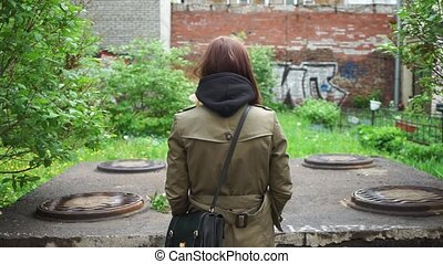 a girl in a raincoat stands with her back to us in front of ...