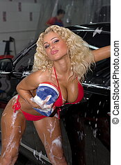 A girl in a red bathing suit washing a car