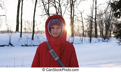 A girl in a red down jacket walking and looking directly into the camera in the woods in winter on a sunset background, slow motion