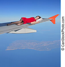 A girl in a red dress is flying on a wing of an aircraft