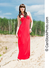 A girl in a red dress posing