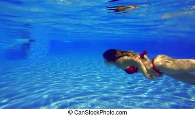 girl in a red swimsuit swims under water in the pool