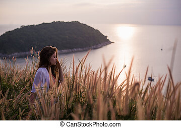 a girl in a shirt is standing by the sea with wheat in her hands