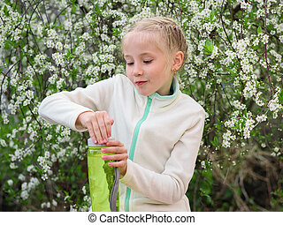 A girl in a sports jacket trying to close the bottle with a refreshing drink near the cherry tree.