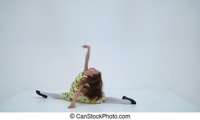 Beautiful girl sitting on a twine on the floor, charming long-haired girl in a summer dress practicing acrobatic exercises, flexible child in casual clothes on a white background
