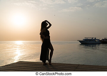A girl in a swimsuit and a cloak is standing on the pier and meets the dawn