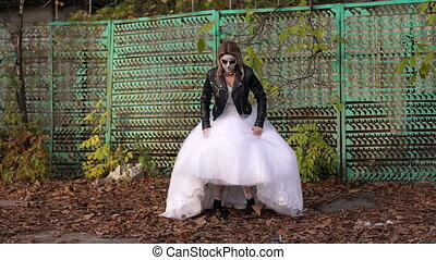 A girl in a wedding dress with a terrible make-up on her face in the autumn.