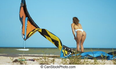 A girl in a white bathing suit puffs a kite with a pump on the seashore