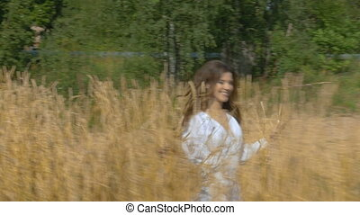 A girl in a white dress runs across the field with wheat.