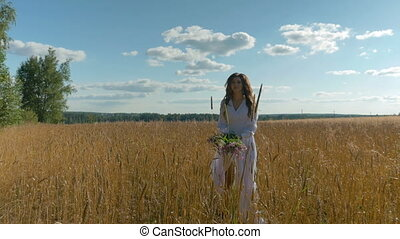 A girl in a white dress throws wild flowers up and runs along the wheat field.