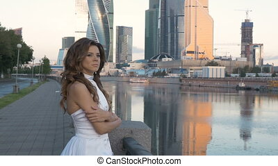 A girl in a white suit, stands alone on the city embankment.