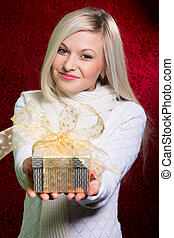 A girl in a white sweater with a gift looking at the camera