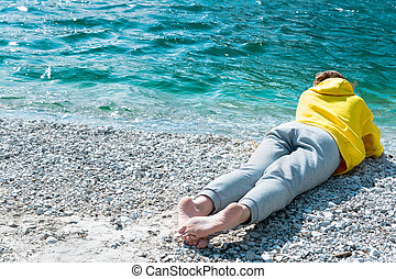 A girl in a yellow hoodie lies on the seashore and looks into the distance.