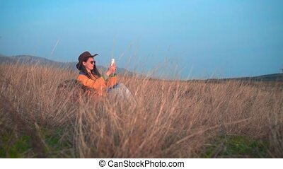 A girl in a yellow jacket, a leather cowboy hat and glasses is sitting in the grass and making a photo on the phone.