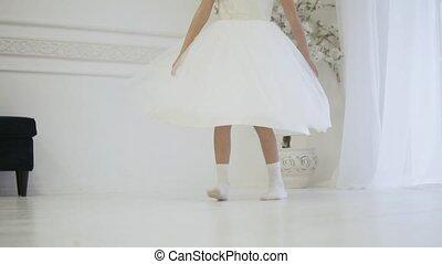 A girl in an elegant white dress whirl in dance. Her dress...