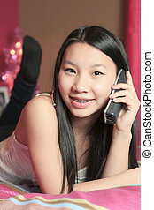 Girl in bedroom taling on the phone