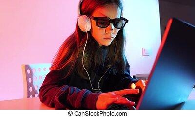 a girl in dark clothes, headphones and 3d glasses works at night at computer. igroman. Hacker. illegal activities on the Internet, hacking websites and downloading unlicensed movies.