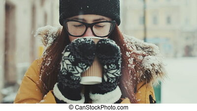 A girl in glasses walks around the city and drinks hot coffee. A smiling woman is drinking a milkshake while walking along a winter city street. Portrait of a beautiful brunette close up
