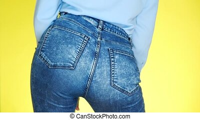 a girl in jeans with beautiful round buttocks is sexually moving. close-up. 4k, slow motion, colored yellow background