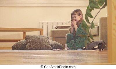 A girl in nice green dress eating sweet