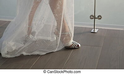A girl in peignoir and legs in high-heeled shoes - The girl...