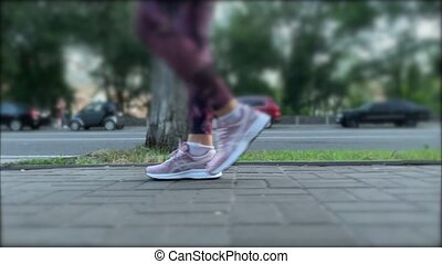Steps of a woman in purple sports shoes on paving tile. ...