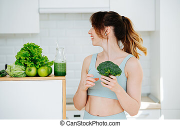 A girl in sportswear standing in the kitchen and holding broccoli in her hands