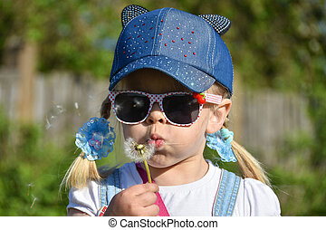 A girl in sunglasses in the field is blowing strongly at a flower dandelion, close-up, summer