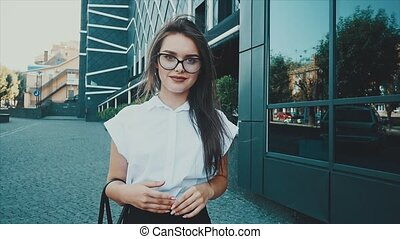 A girl in the business district of the city goes to a business partner meeting. Young woman in business clothes. Business style.