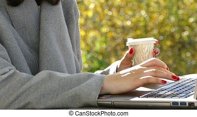 A girl in the nature sits with a laptop and drinks coffee.