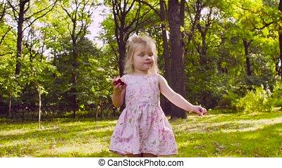 A girl in the park eating garnet